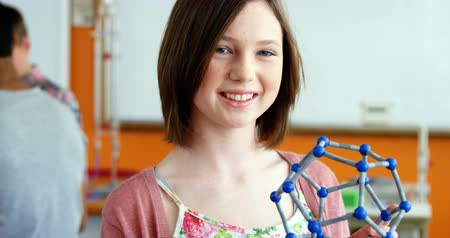 chemistry : Portrait of happy schoolgirl experimenting molecule model in laboratory at school