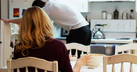 tigela : Man serving breakfast to woman in kitchen at home Vídeos