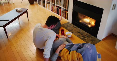 bonding : Couple relaxing near fireplace in living room at home Stock Footage