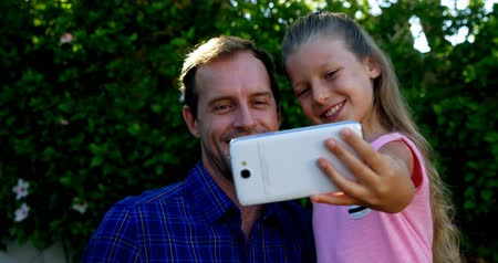 любовь : Father and daughter taking selfie on mobile phone in park on a sunny day Стоковые видеозаписи