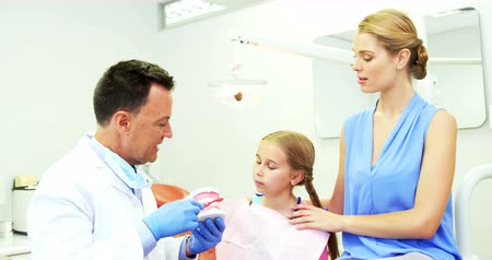 escovação : Dentist showing young patient how to brush teeth in dental clinic