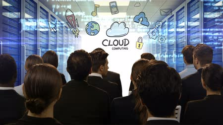 setting : Business people looking at digital screen showing cloud computing against server room background