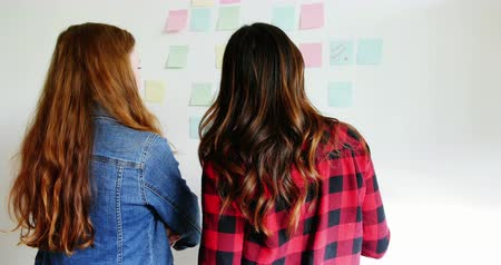 executivo : Rear view of female executives writing on sticky notes in office