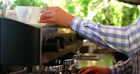 portafilter : Male owner arranging cup and saucer at outdoor café