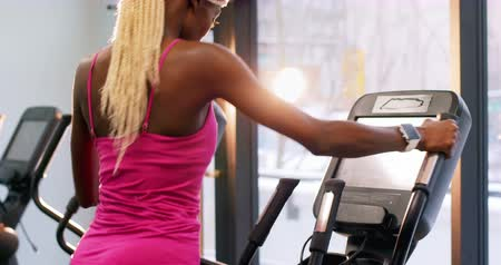 тренер : Fit woman exercising on cross trainer in gym