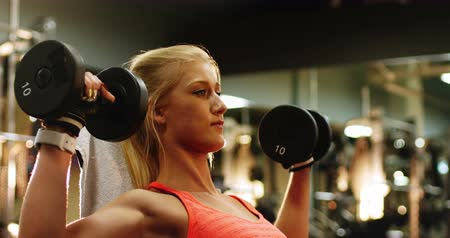 focalizada : Fit woman exercising with dumbbell in gym Vídeos