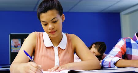estudioso : Attentive students studying in classroom at school Stock Footage