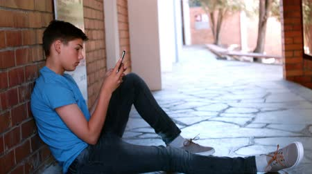 teenager : Schoolboy sitting in corridor and using mobile phone at school
