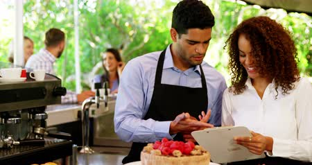 proprietário : Male and female waiter discussing over clipboard at outdoor café