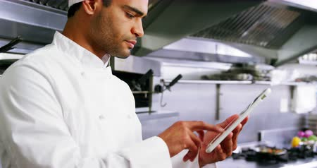 отель : Male chef using digital tablet in commercial kitchen at hotel