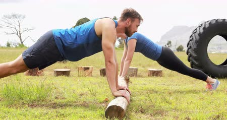 ботинок : Fit man and woman doing pushup during obstacle course in boot camp