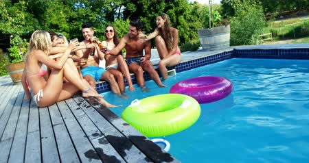 inflável : Group of friends having fun at poolside on a sunny day