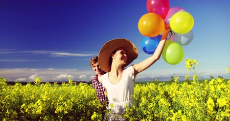 двадцатые годы : Romantic couple holding colorful balloons and running in mustard field on a sunny day