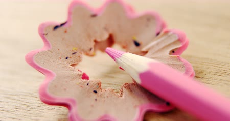 sharpened : Close-up of pink color pencil with pencil shaving on wooden background
