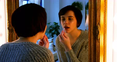 applying : Woman applying lipstick while looking in mirror at home