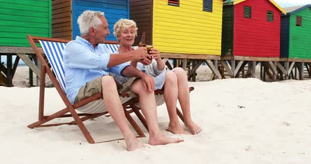 elliler : Senior couple toasting drinks near colorful beach hut on a sunny day