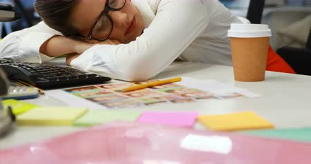 усталый : Female graphic designer sleeping at desk in office