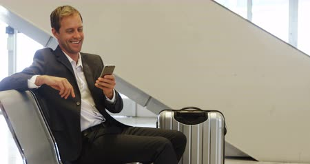 полет : Businessman using a smartphone at the airport