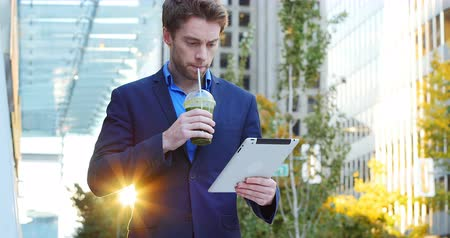 adam : Businessman using digital tablet while having juice near office building