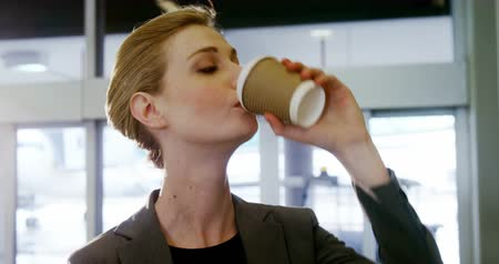içme : Businesswoman having coffee from disposable cup at the airport Stok Video