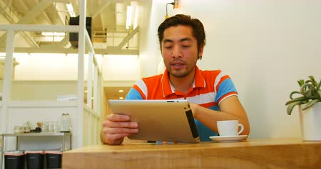 kafeterya : Man using digital tablet while having coffee cup on table in coffee shop Stok Video