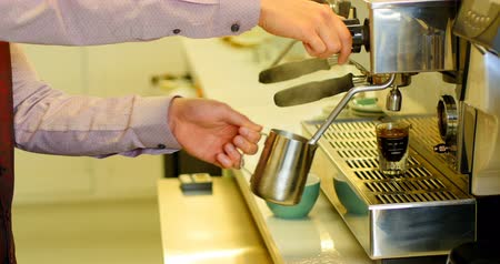 kafeterya : Mid section of waiter making espresso in cafe