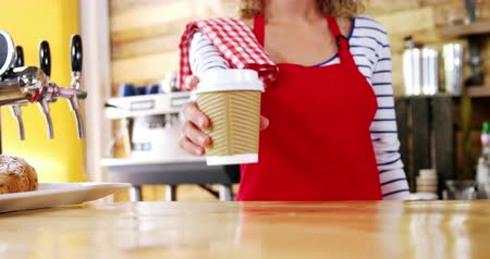 porce : Smiling waitress serving a coffee at counter in café