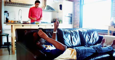 bonding : Man using virtual reality headset while friend preparing food at home Stock Footage