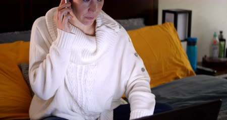 rolety : Woman talking on mobile phone and using laptop on bed in bedroom Wideo