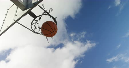 abroncs : Basketball player scoring a dunk in basketball court outdoors