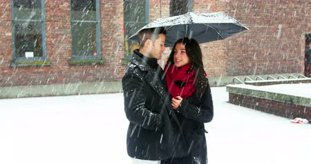 xale : Couple interacting with each other under umbrella during snowfall