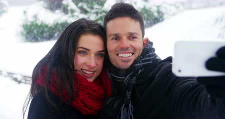 bonding : Smiling couple taking selfie on mobile phone during winter