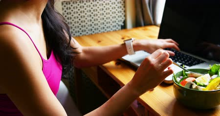 coreano : Woman using laptop while having breakfast at home