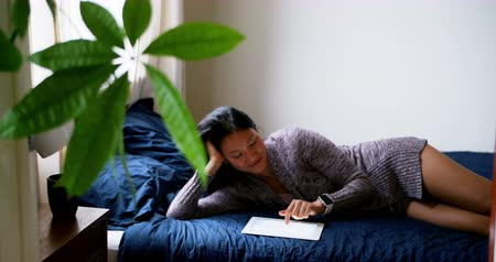 coreano : Woman using digital tablet while relaxing on bed in bedroom Stock Footage