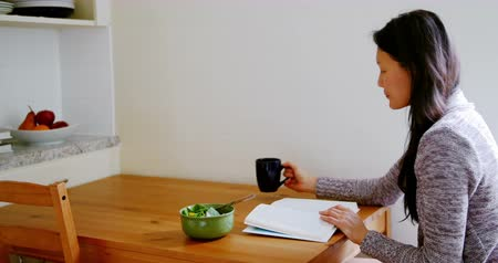 coreano : Woman reading book while having coffee in kitchen at home