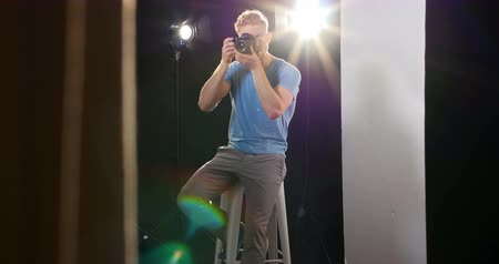 ajustando : Male photographer photographing with digital camera in studio