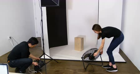 ajustando : Photographer and colleague preparing for photo shoot in the studio Stock Footage