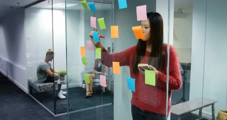 yapışkan : Female executive writing on stick notes in the office