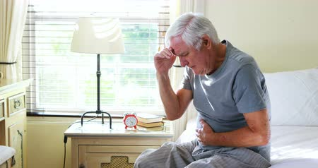 painéis : Unhappy senior man suffering from stomach ache at home