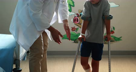 инвалидность : Male doctor assisting injured boy to walk with crutches in hospital
