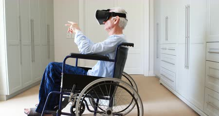 fejhallgató : Senior man on wheelchair using vr headset in bedroom at home Stock mozgókép