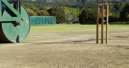 wicket : Cricket roller used to prepare pitch at cricket ground on a sunny day
