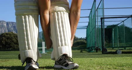 batting pads : Cricket player tying his batting pads during a practice session on cricket ground