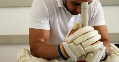 batting pads : Stressed cricket player sitting on bench in dressing room