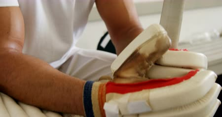 cricket pads : Stressed cricket player sitting on bench in dressing room