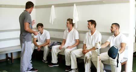 batting pads : Coach interacting with cricket players in dressing room
