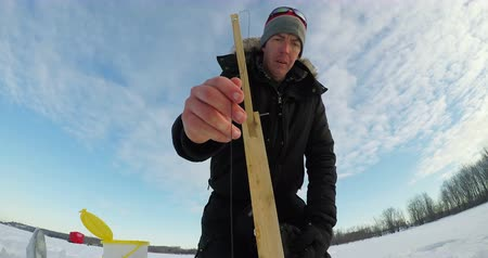 beállítás : Ice fisherman setting up the bait for fishing in snowy region