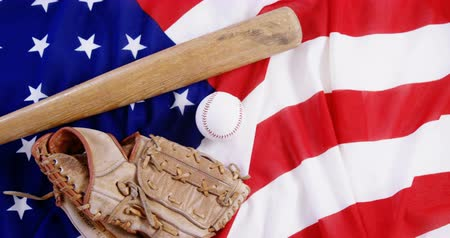определение : Close-up of baseball, baseball bat and baseball gloves on an American flag Стоковые видеозаписи