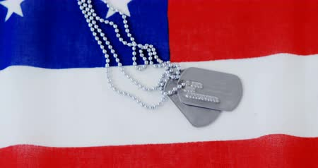 medailónek : Close-up of dog tag chain on an American flag