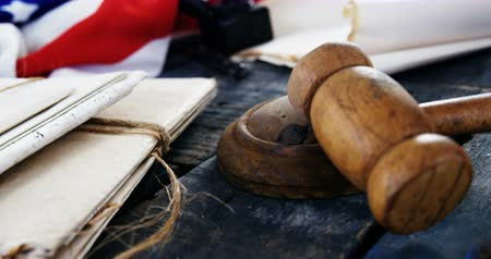 judgment day : Close-up of gavel and legal documents arranged on American flag